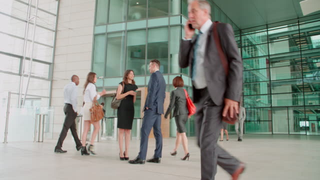 Business people passing couple in foyer of a modern building video