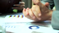 Business people pointing and interacting with there document information during meeting at office. video