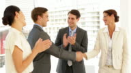 Business people shaking hands at interview while others applaud video