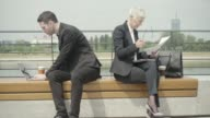Business People sitting on bench and looking at papers. video