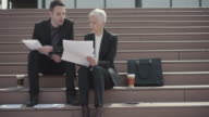 4K: Business People sitting on stairs and looking at papers. video