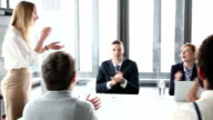 Business people smiling and clapping on a meeting in conference room video