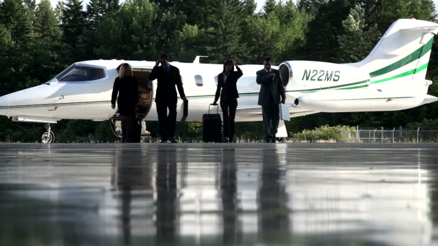 Business people walk away from jet video
