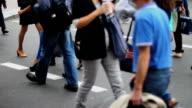 Business people walk on crossroad pedestrians, city daytime video