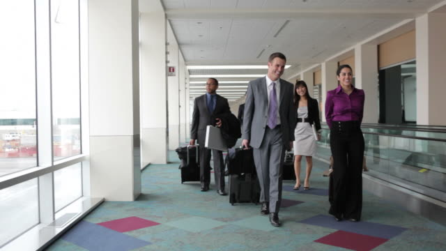 Business people walk through airport lobby video