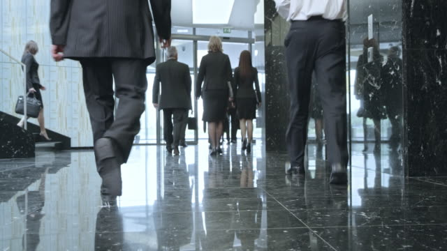 LD Business people walking through a lobby and out of the building video