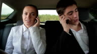 Business people with mobile phones in the car video