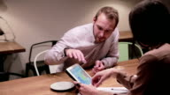 Business people working with tablet in cafe video