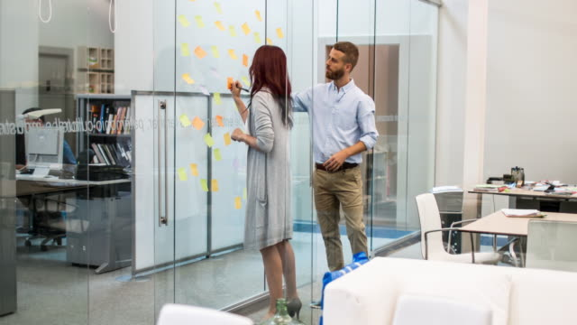 Business people writing ideas at adhesive notes in conference room video