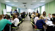 Business performance of a great number of students. Large modern classroom in which there are several projectors. new kind of training for the development of business skills in students. Camera moves among the teams of students video
