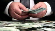 Business person counting bundle of US 100 dollars bank notes video