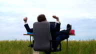 Business person taking break at office in a green field video