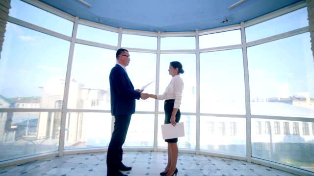 Business, real estate concept. Man and woman shaking hands at office video
