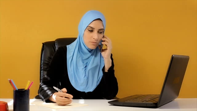Business secretary in Arab company talking on mobile phone video