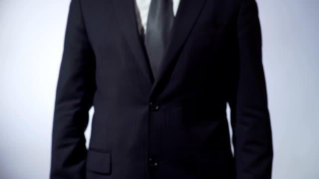 Business strategy written on blackboard, male in black suit holding sign, career video