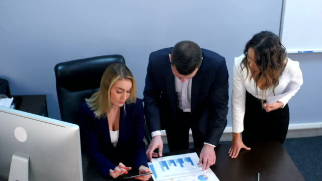 Business team discussing documents in office video