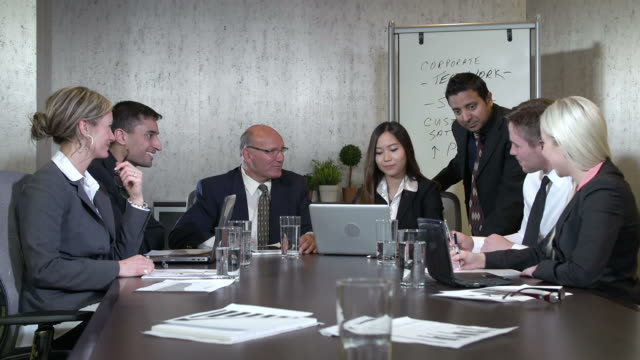 Business team in a boardroom meeting video