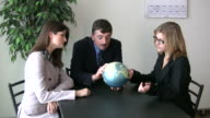 (HD1080i) Business Team Looks for Location on Globe video