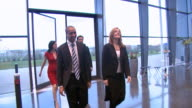 Business team walk through large office building video