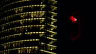 Business tower with a traffic light in the foreground. video