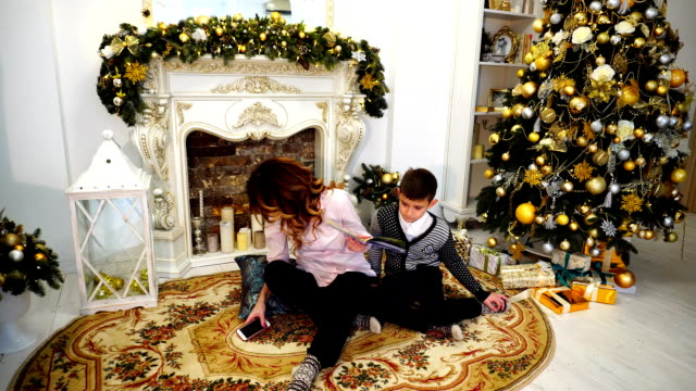 Business woman and modern mother manage everything and take care of children, and she decides working questions on phone while in living room, decorated for holidays with fireplace and tall tree video