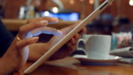 Business woman checking emails on Digital tablet in cafe video