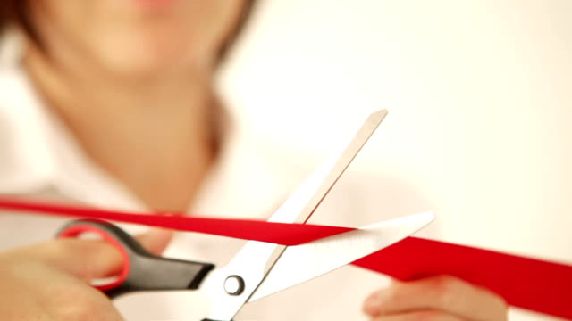 Business woman cutting the red ribbon with scissors and open the event video