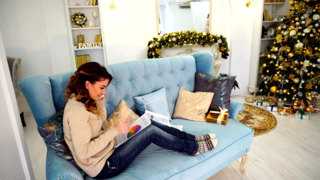 Business woman decides last working questions before holidays and talks on phone, sitting on blue sofa in festively decorated room with Christmas tree and fireplace during day video