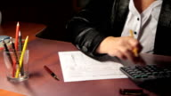 business woman fills out a 1040 tax form. slider shot. video