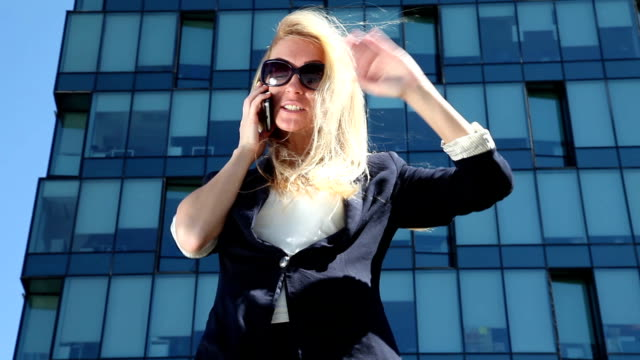 Business woman gives orders on her cell phone video