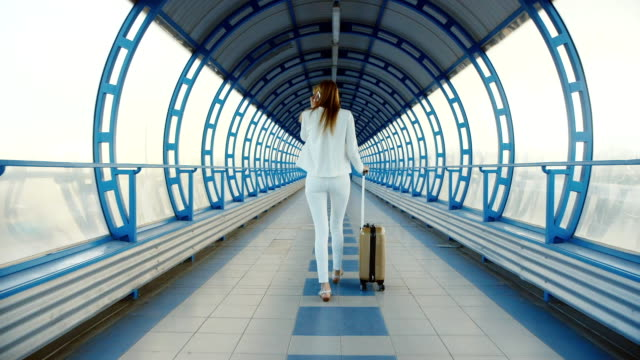 business woman in a white suit goes on teklyannomu tunnel. Lucky bag on wheels. Back view video