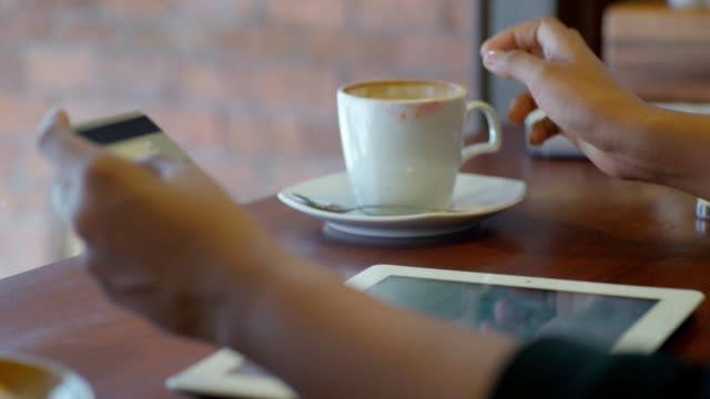 Business woman shopping online with tablet PC in coffee cafe video