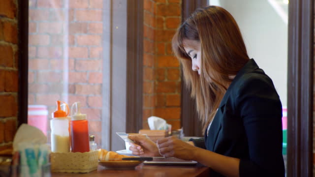 Business woman shopping online with tablet PC  in restaurant video
