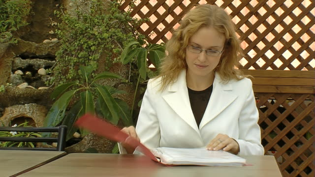 Business woman sits at the table in cafe video