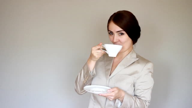 Business woman smiling, looking at camera and drinking coffee. or tea. Break. Young woman winks video