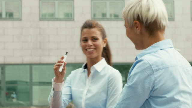 Business woman smoking cigarette near office building video