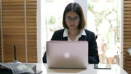 Business woman typing on keyboard and working with laptop video