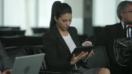 Business woman uses a digital tablet in airport lobby video