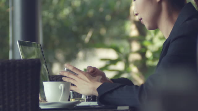 business woman using laptop and drinking coffee video