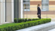 business woman with tablet computer goes around office building. slow motion, out of the building video