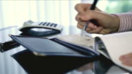 Business woman writing a cheque in office video