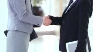 SLO MO LD Business women shaking hands in hallway video