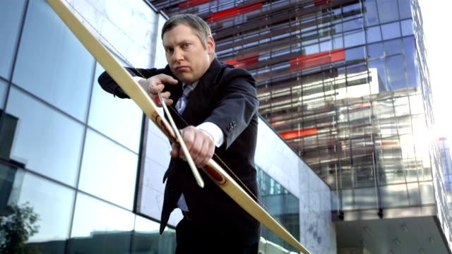 HD DOLLY: Businessman Aiming An Arrow At Camera video