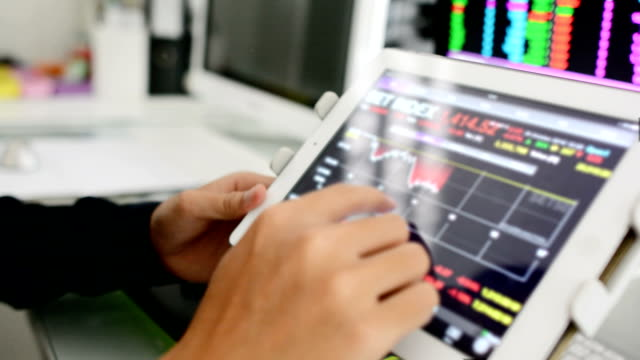 Businessman analysis stockmarket with digital tablet and laptop in office video