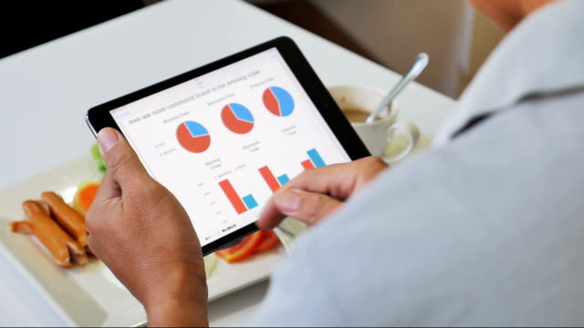 Businessman analyzing market data information on a digital tablet video