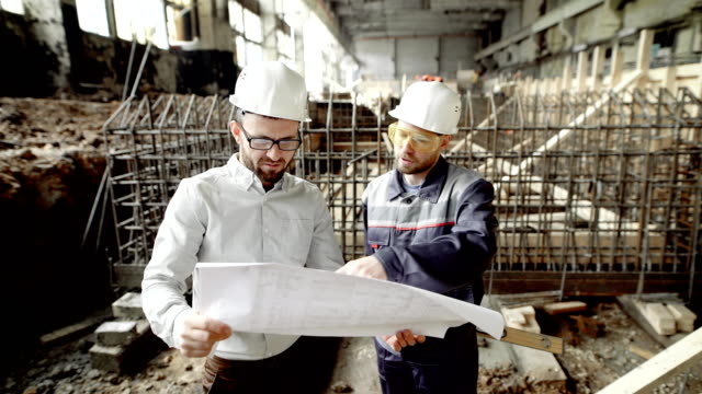 A businessman and a professional worker look at the drawing in order to determine the possibility of upgrading the old factory building video