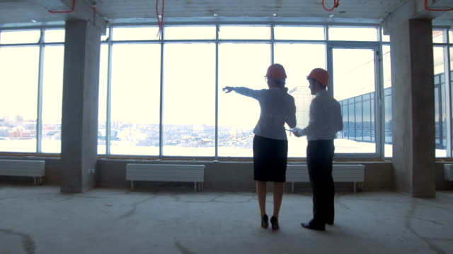 Businessman and business woman in suit, hard hat in a new unfinished office building communicate, discuss blueprint, construction site video