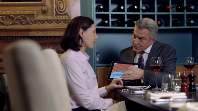 MS Businessman and businesswoman discussing with digital tablet in restaurant video