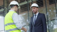 Businessman and Engineer in Hard Hats Having Agreement Handshake on Construction Site. video