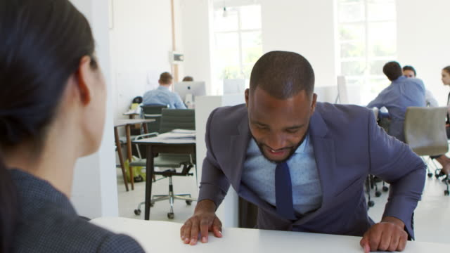 Businessman and woman sitting at desk in an open plan office video